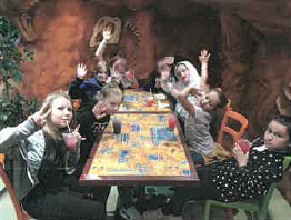 The children of the Triple T Youth Club sitting outside around a table and playing a game.