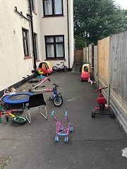 Beresford Mansions with bicycles, a chair and children's toys blocking the pathway outside.