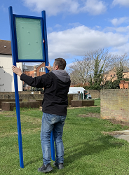 Woodgrange Drive Estate - A man installing the new noticeboard