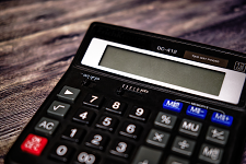 A calculator on top of a wooden surface. Links to our Benefits Calculator page.