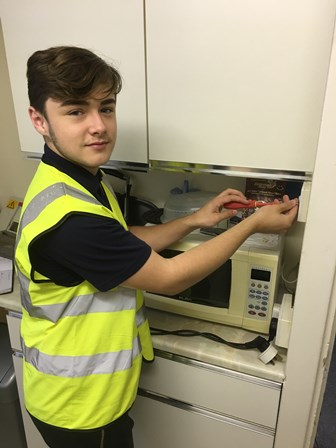 Photograph of Jamie who is a resident and our Electrical repairs partner's apprentice